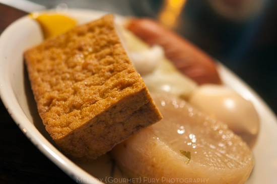 Oden with tofu, egg, fish cake, sausage, daikon, and more  at Late Night Ramen and Oden Cart at Shinjuku Station Tokyo by Melody Fury Photography. Food, Drink, Restaurant Photographer and Writer in Vancouver BC and Austin TX