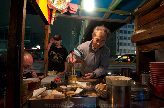 The owner fixes a bowl of oden at Late Night Ramen and Oden Cart at Shinjuku Station Tokyo by Melody Fury Photography. Food, Drink, Restaurant Photographer and Writer in Vancouver BC and Austin TX